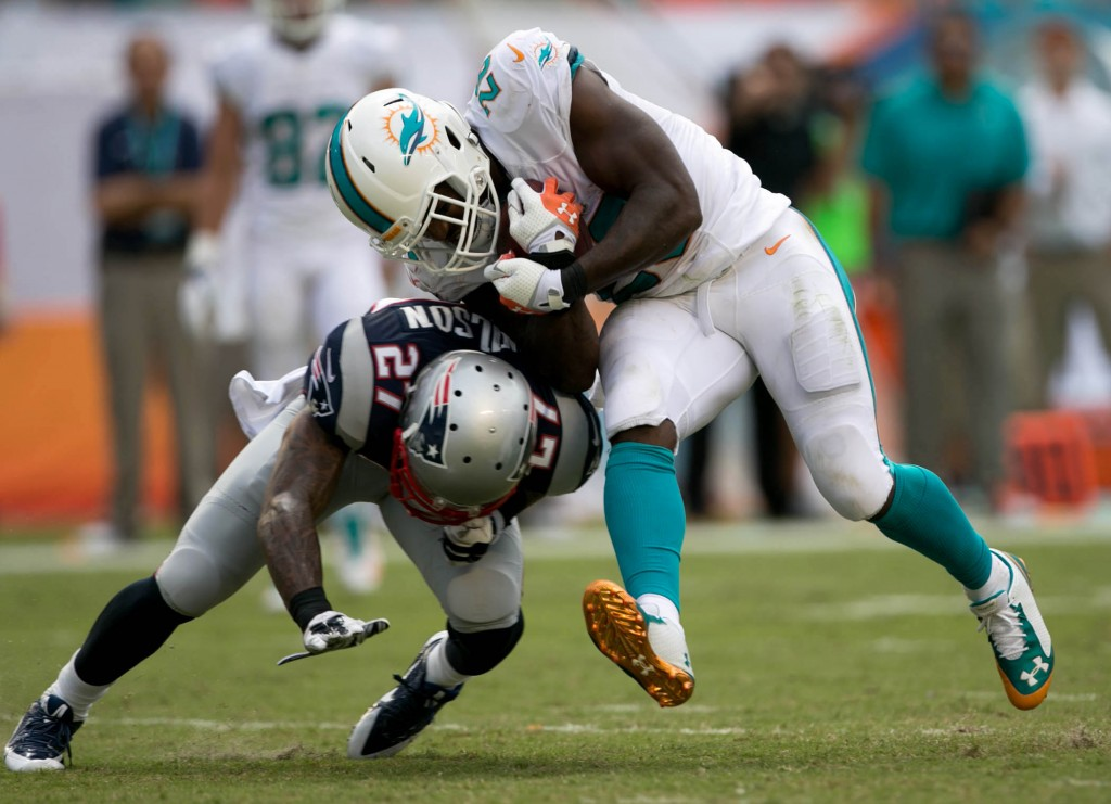 Miami Dolphins running back Lamar Miller (26) runs over New England Patriots strong safety Tavon Wilson (27) at Sun Life Stadium in Miami Gardens, Florida on September 7, 2014. (Allen Eyestone / The Palm Beach Post)