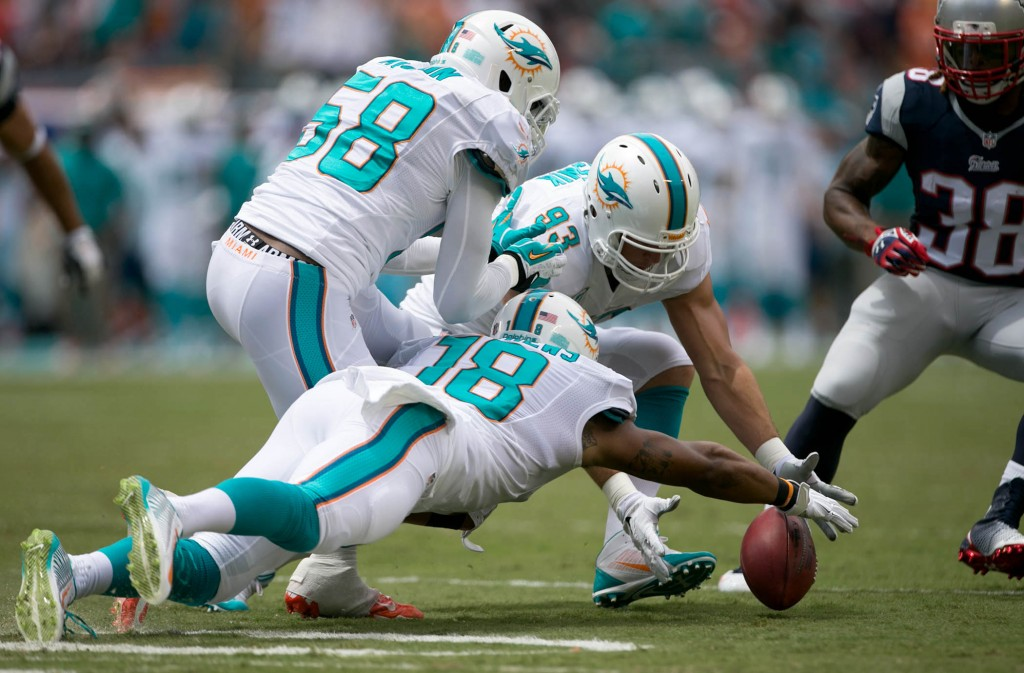 Miami Dolphins Chris McCain (58),  Rishard Matthews (18) and Jason Trusnik (93) chase after and recover a blocked punt in the first quarter at Sun Life Stadium in Miami Gardens, Florida on September 7, 2014. (Allen Eyestone / The Palm Beach Post)