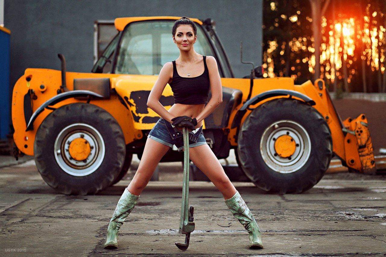 Construction worker girl with bulldoezer and wrench
